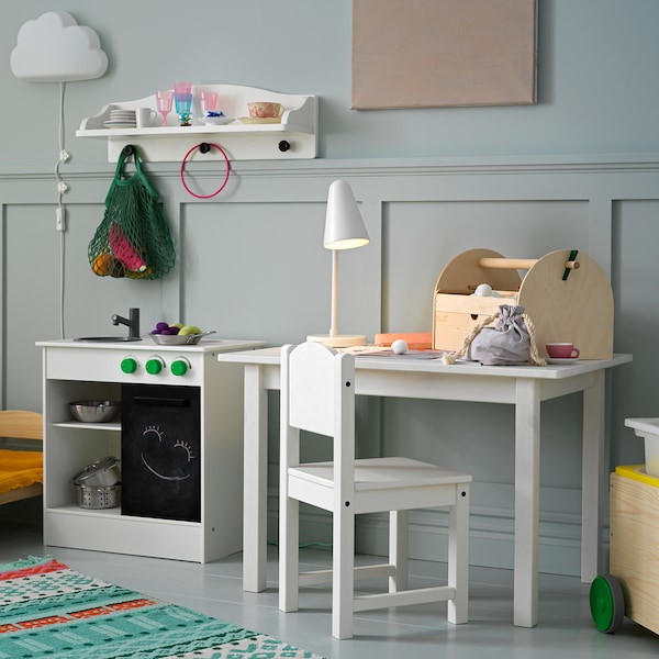 A children's chair and a children's table with a table lamp and crafts on top, and they stand next to a white play kitchen.