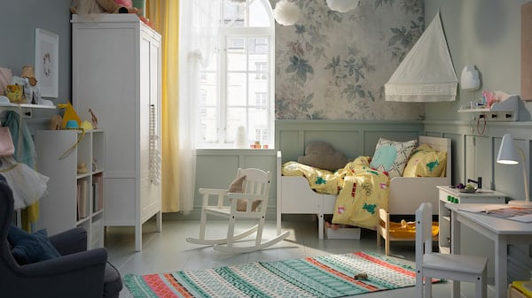 A children's room with a bed, bed canopy, wardrobe, table and chair in white. A colourful rug lies across the floor.