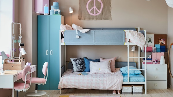 A children's room with a bed in pine, a wall that's painted like mountains, a rug with a boat pattern and lots of soft toys.