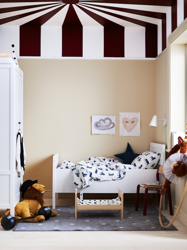A children's room with a circus inspired painted ceiling, a white SUNDVIK extendable bed and white and dark blue bed linen.