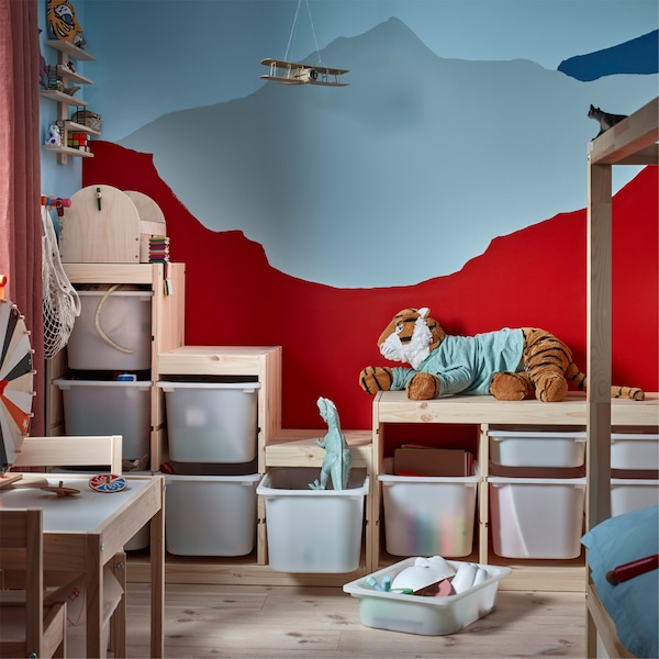 A children's room with a mountain-looking pattern painted on the wall and lots of storage boxes in front of it that store toys.