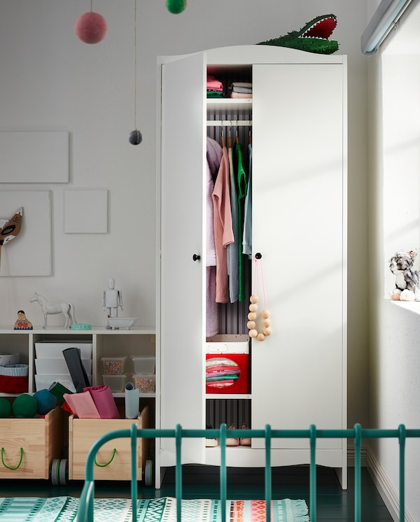 A children's room with a wardrobe with one door that's open. Boxes and both hanging and folded clothes are stored inside.