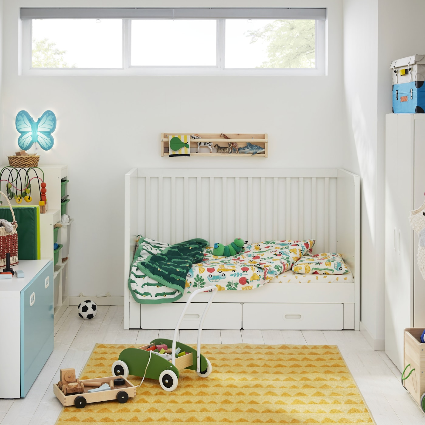A children's room with a white cot, a yellow rug, a white wardrobe, a green toddle truck and a butterfly-shaped wall lamp.