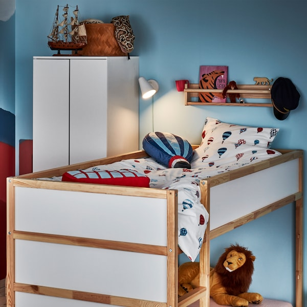 A children's room with blue walls and a KURA reversible bed with bed textiles on top and a cosy play corner in the bottom.