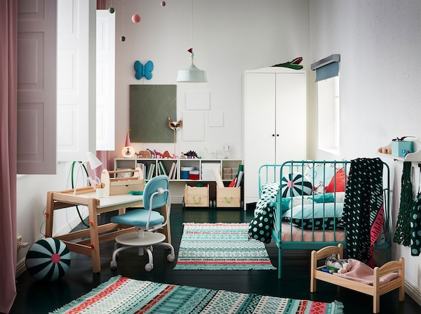A children's room with colourful rugs, a bed frame in turquoise, a white wardrobe, pink curtains and a children's desk.