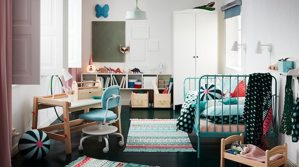 A children's room with colourful rugs, a bed frame in turquoise, a white wardrobe, a doll's bed and a children's desk.