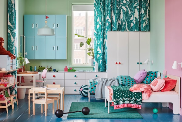 A children's room with white wardrobes and chests of drawers, two extendable bed frames, a green rug and blue wall cabinets.