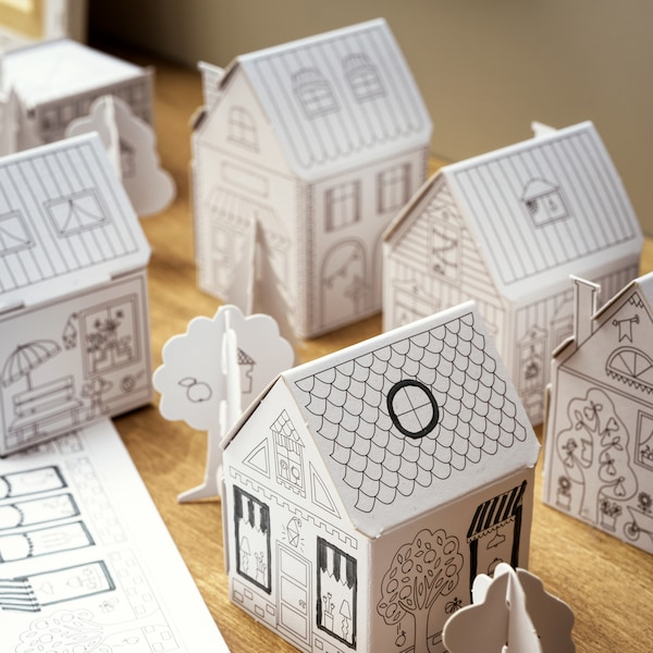 A children's toy MÅLA cardboard town with different houses and trees, placed on a wooden surface.
