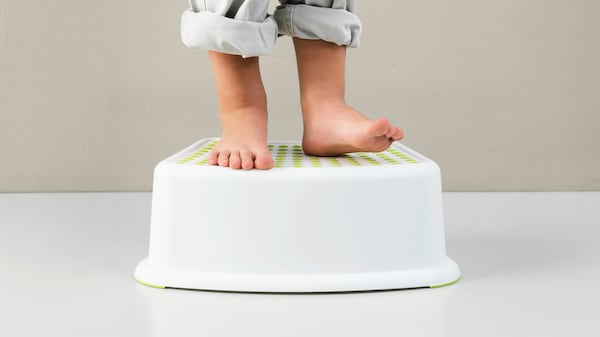 A child's bare feet standing on a plastic stool with their pants rolled up past their ankles.