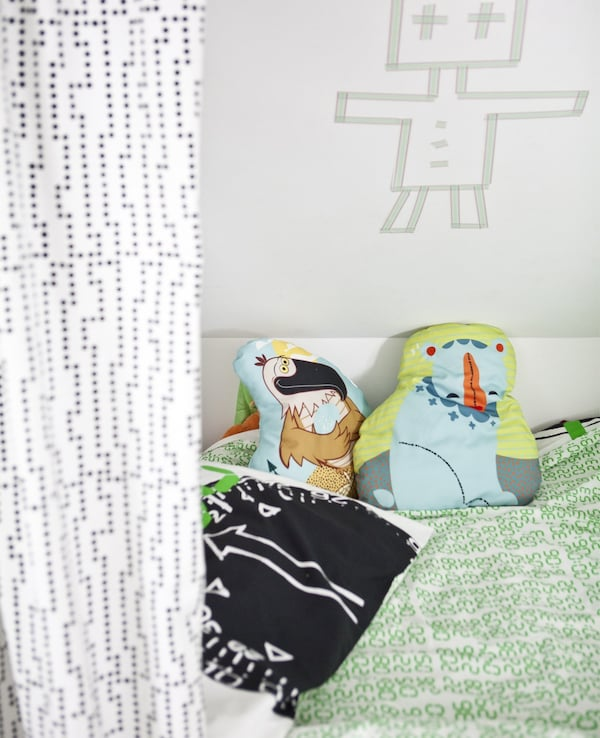 A child's bed with colourful bedding and cushions.
