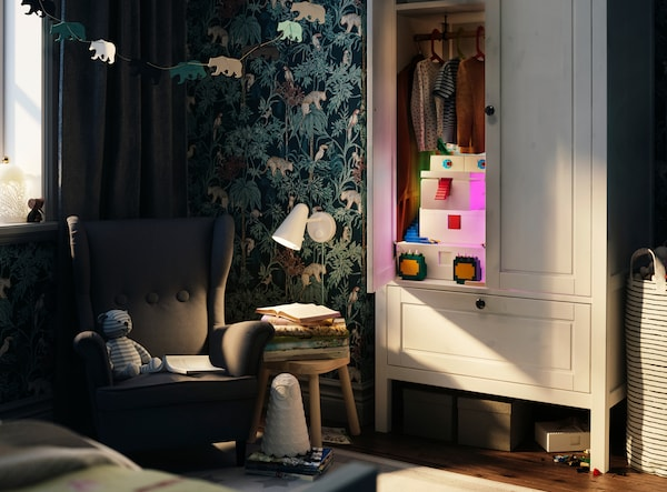 A child's bedroom that has a white wardrobe at its centre, with five BYGGLEK boxes inside decorated like a monster.