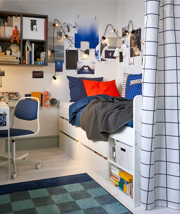 A child's bedroom with a single bed and under-bed storage, wall-mounted storage and a privacy curtain.