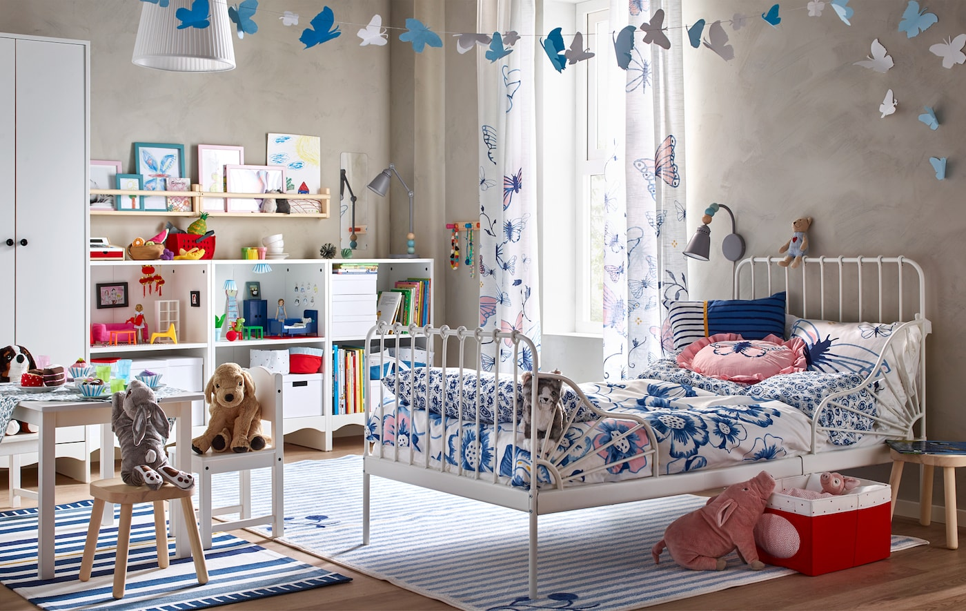 A child's bedroom with white bed, floral textiles, a mini table and chairs, and a storage unit full of books, boxes and toys.