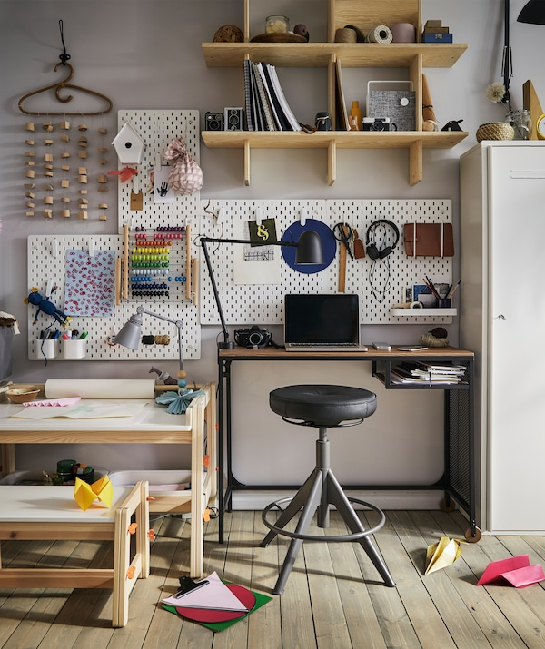 A child's desk with craft materials next to an adult's desk with stool and pegboards on the wall.