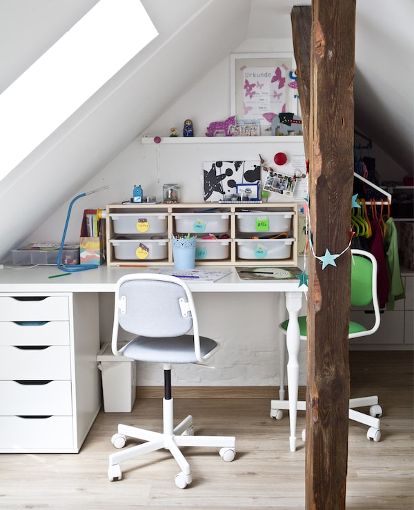 A child's desk with storage boxes and two chairs.