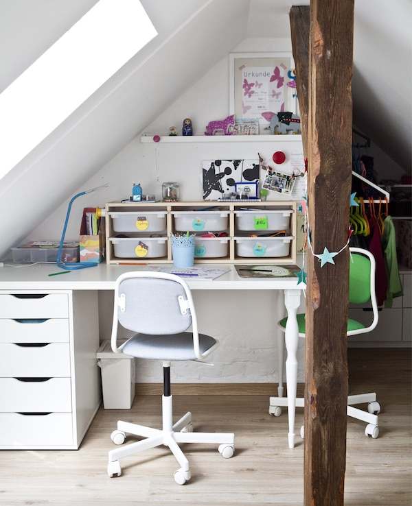 A child's desk with storage boxes and two office chairs in a white bedroom.
