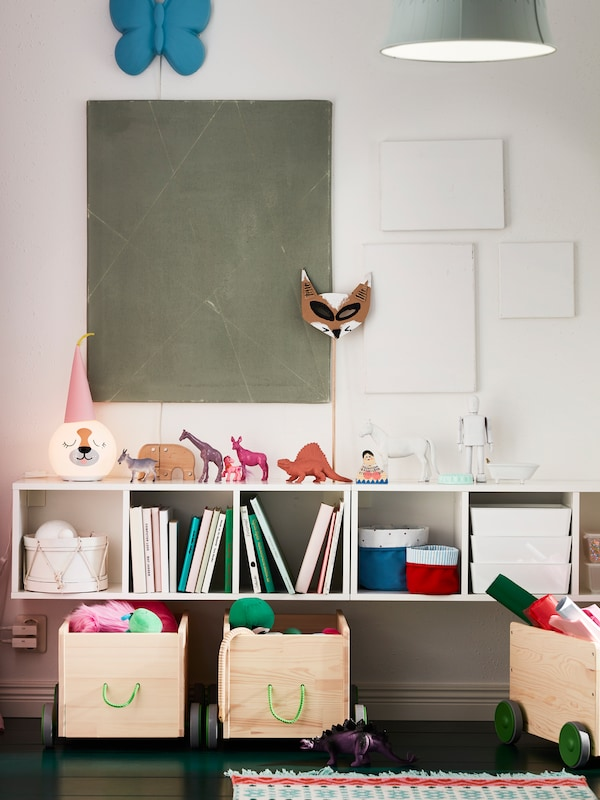 A child's nursery bedroom with IKEA FLISAT storage boxes on wheels and SMÅGÖRA modular wall storage with toy animals.
