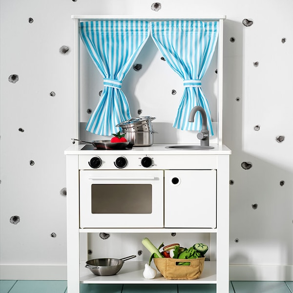 A child's play kitchen in white, with striped blue curtains.