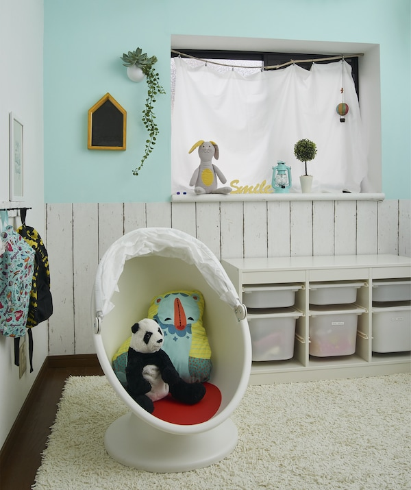 A child's playroom with storage boxes and soft toys in a child's armchair on a rug.