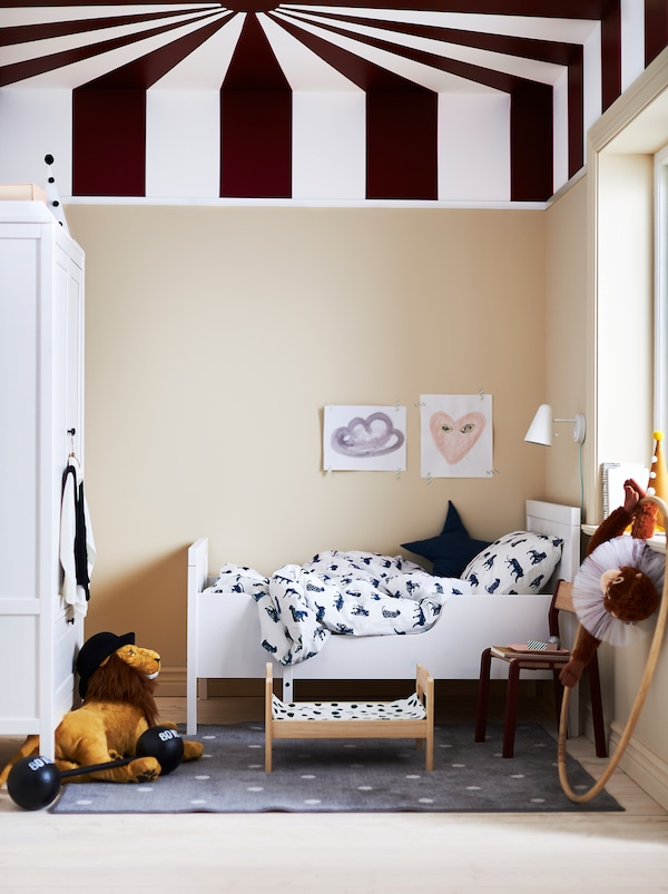 A child's room with a SUNDVIK extendable bed, soft toys and a ceiling painted with radiating stripes like a circus-tent roof.