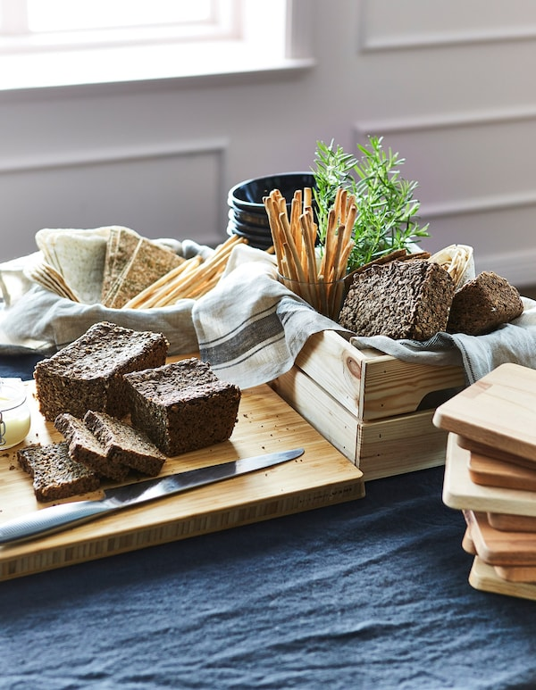 A chopping board and wooden crate filled will bread, crackers and bread sticks on a table.