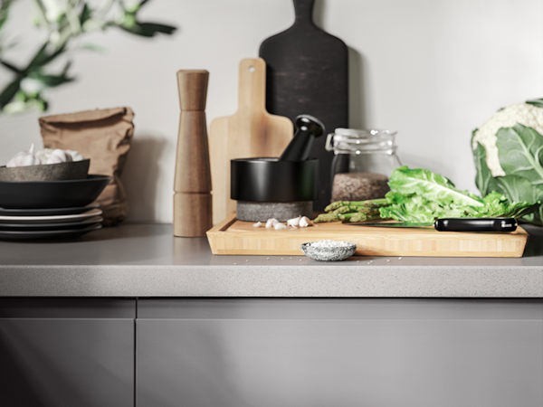 A chopping board with vegetables sitting on a grey KASKER countertop.