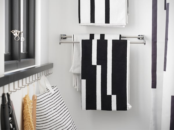 A chrome-plated towel rail where black/white striped towels hang. It's mounted next to the shower.