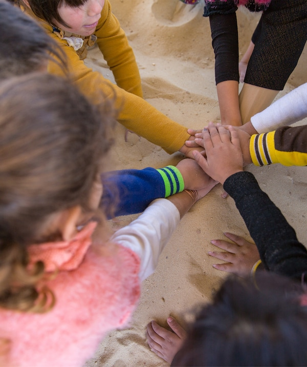 A circle of children putting their hands together in the centre.