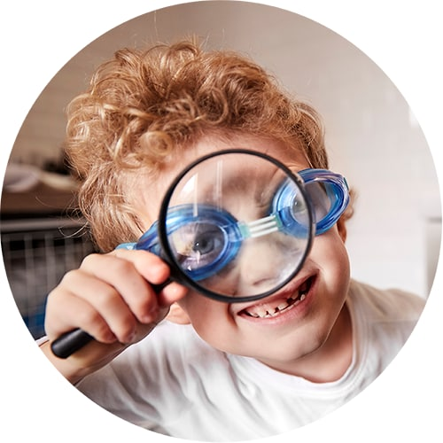 A circular image of a child wearing goggles holding a magnifying glass to his face.