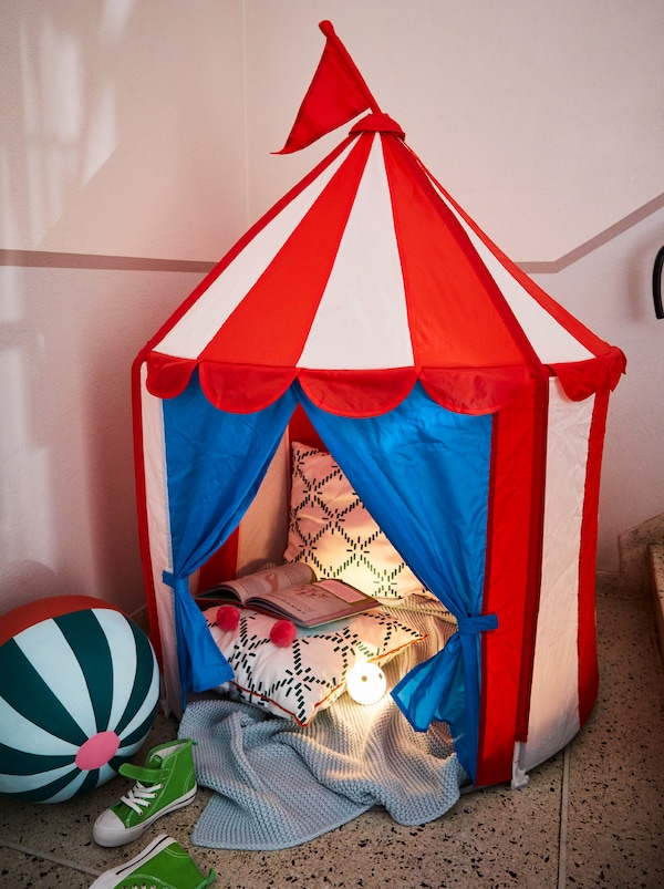 A CIRKUSTÄLT children's tent at the base of a staircase, filled with soft textiles, a KÄPPHÄST soft toy and an open book.