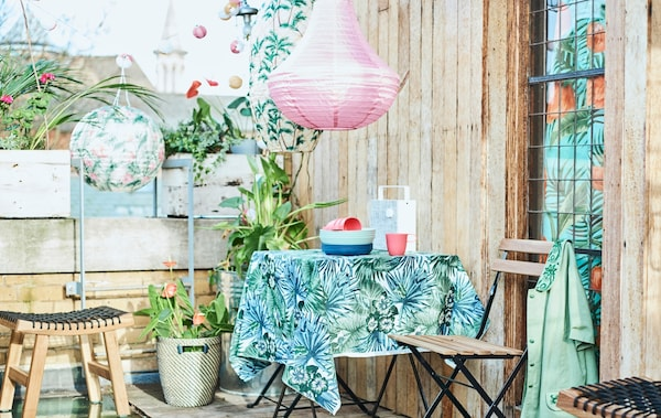 A city roof terrace with a patio table covered with leaf-print fabric, folding chairs, potted plants and coloured lanterns.