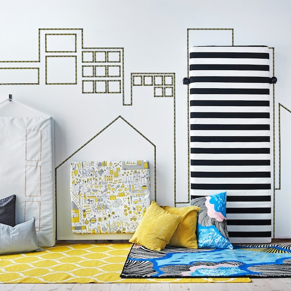 A city skyline is created on a bedroom wall using decorative tape and mattresses covered in textiles.