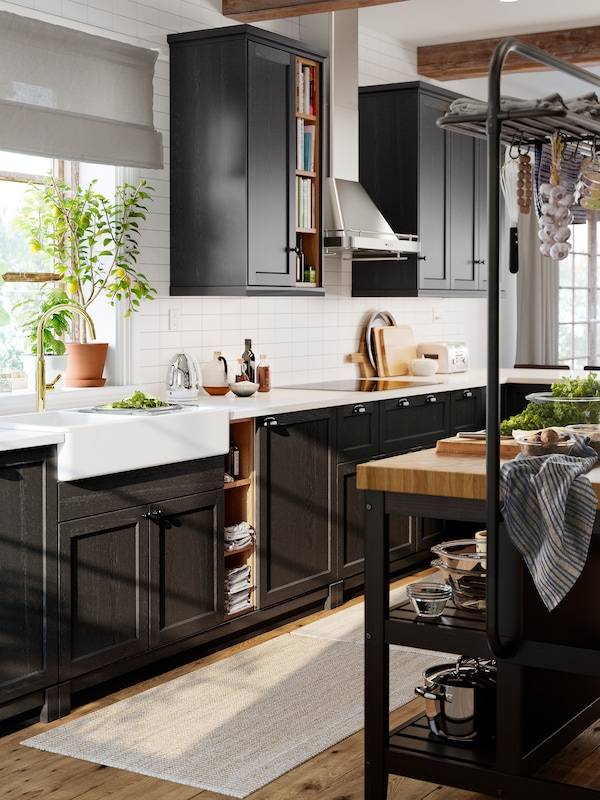 A classic style kitchen with stained black cabinet fronts, a white worktop and a white sink with visible front.