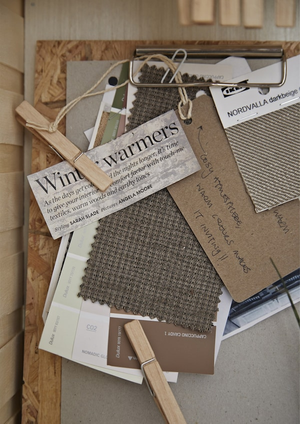 A clipboard with clippings and textile samples.