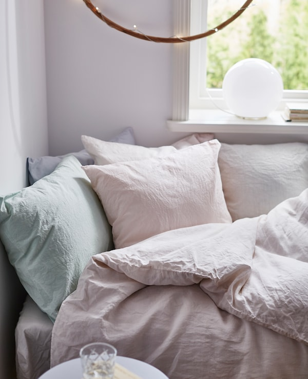 A close-up image of a cozy bed with hand-dyed pastel bed linens.