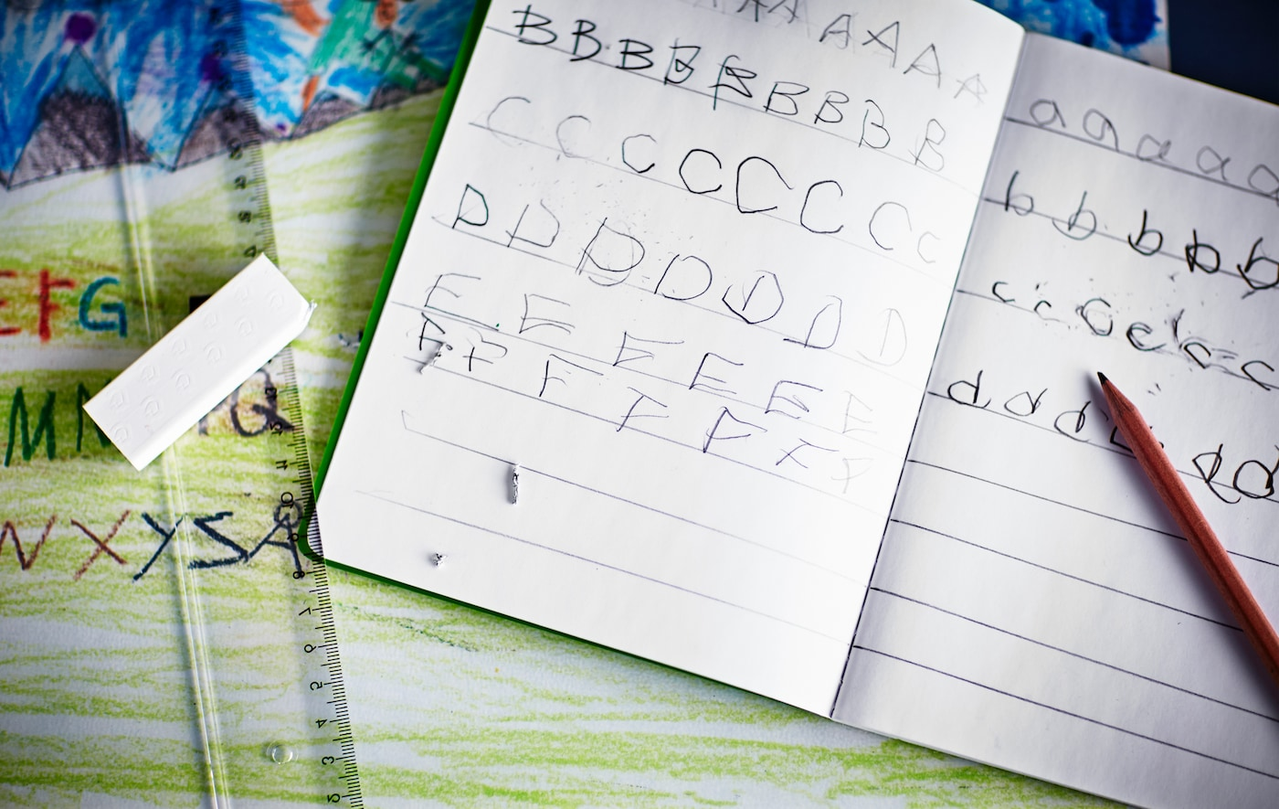 A close-up image of a notebook with children's handwriting as they practice the English alphabet.