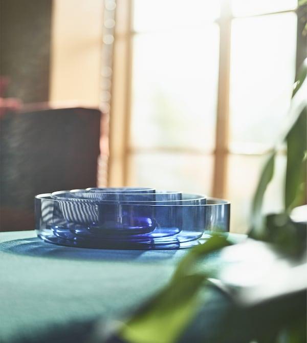 A close-up image of a set of blue glass serving bowls.