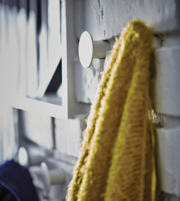 A close-up image of a sweater hanging from a hook on the wall.