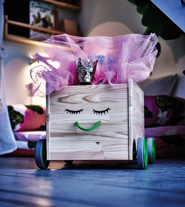 A close-up image of a toy box on wheels, decorated with a smiley face.