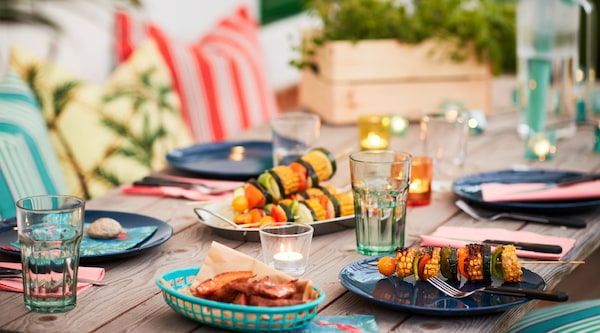 A close up image of an outdoor table set for a summer party with colourful dishes, bbq kabobs, string lights and colourful pillows in the background.