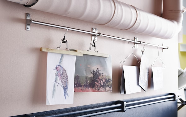 A close-up image of artwork hung with hanger from a rail mounted between pipes.