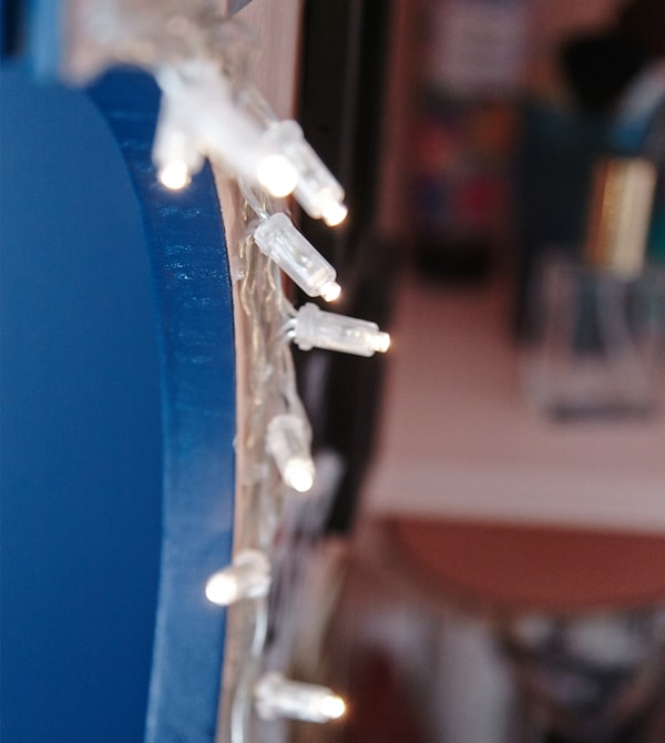 A close-up image of fairy lights hanging in the vanity cabinet.