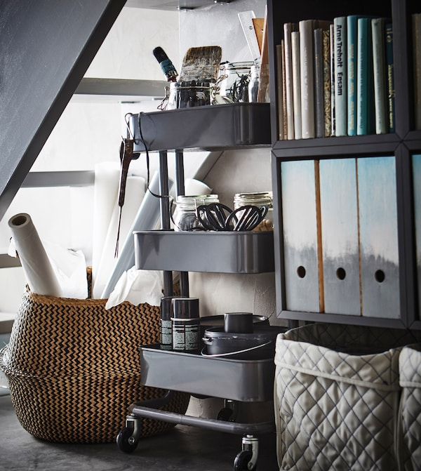 A close-up image of home office supplies stored under a staircase in a basket, a trolley, and a bookshelf.