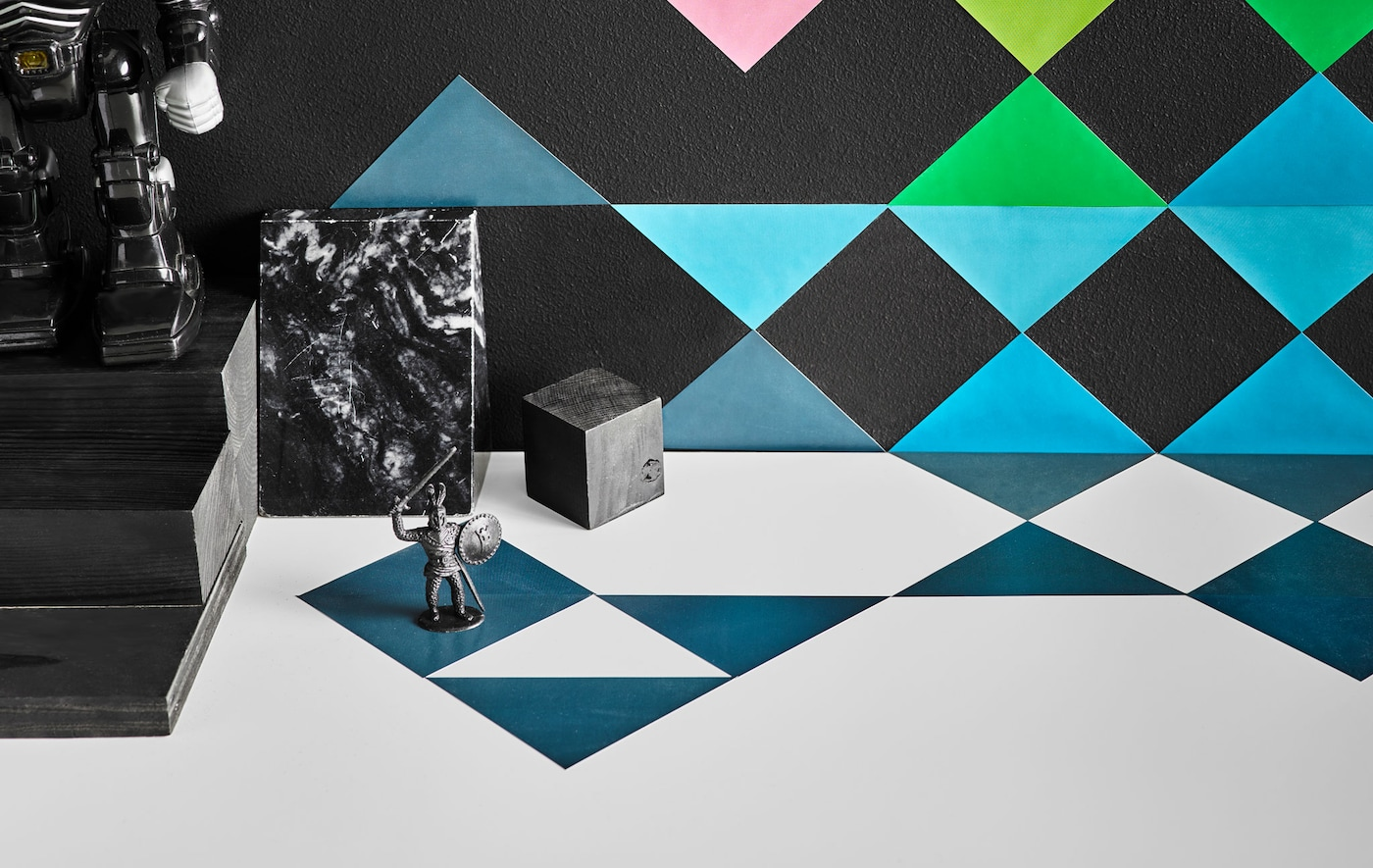 A close up image of multi-coloured triangular stickers arranged decoratively on a wall and a kid's desk.