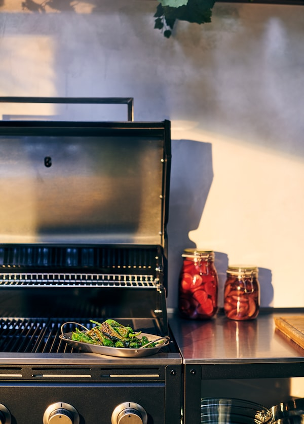 A close up image of the GRILLSKÄR barbecue grill with the KORKEN jars and GRILLSKÄR barbecue tray.
