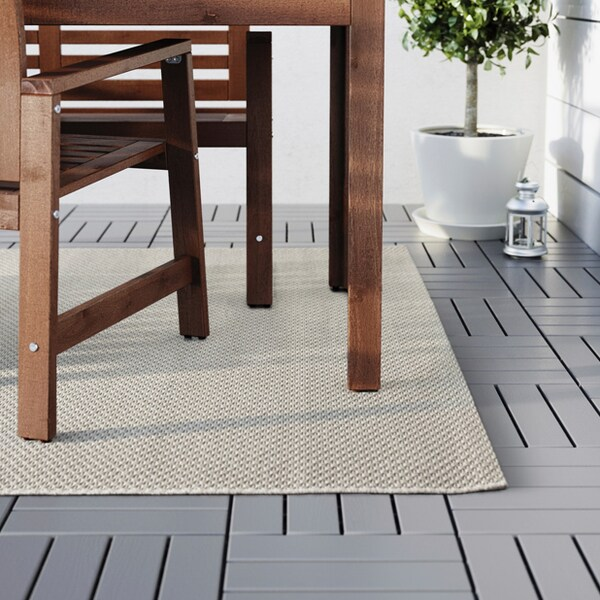 A close up image of the MORUM tan rug sitting under an outdoor dining set.
