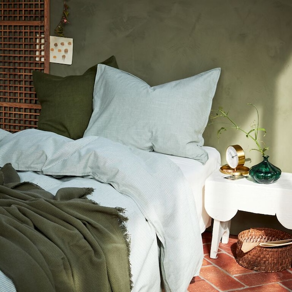 A close up of a bed with BERGPALM bed linen and a dark green ODDRUN throw.