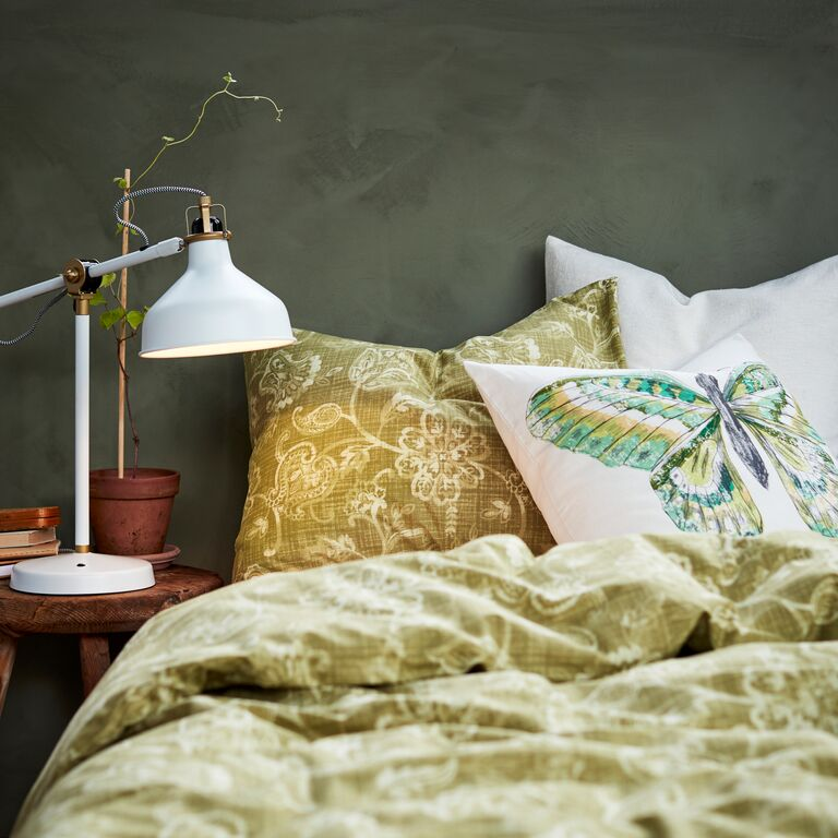 A close up of a bed with JUNIMAGNOLIA bed linen and a tactile VIGDIS cushion.