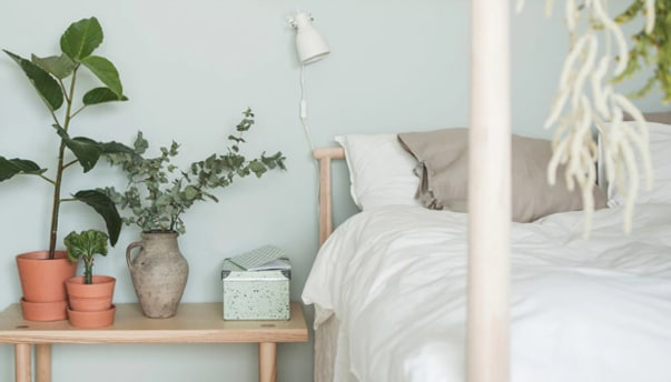 A close-up of a bed with lightly colored, natural textiles against a light green wall and a low ash bedside table with plants and a storage box