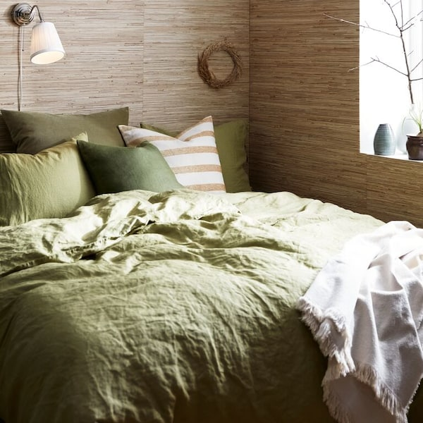 A close up of a bed with PUDERVIVA bed sheets, pillow cases and soft KNIPPARV cushions.